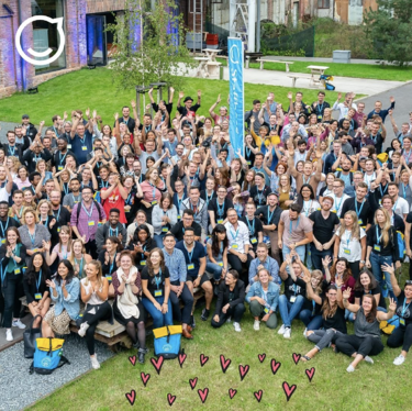Staffbase's team smiling and raising their arms for a photo outside