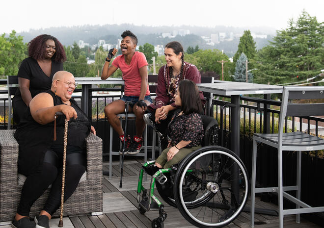 Five disabled people of color with canes, prosthetic legs, and a wheelchair sit on a rooftop deck, laughing and sharing stories.